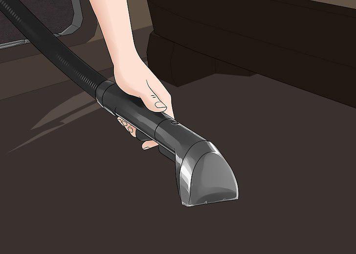 sử dụng máy hút bụi để làm sạch nội thất ô tô.